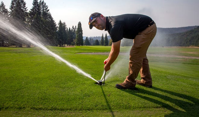 Tokatee Golf Club superintendent Ty Patton turns on a sprinkler at the course. An emergency generator enabled the course to keep its water pumps working which meant the course's greens could be maintained.