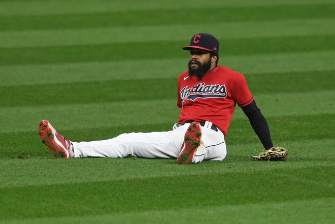 Cleveland Indians' Delino DeShields sits on the ground after committing an error during the ninth inning of Game 2 of the eam's American League wild-card baseball series against the New York Yankees, early Thursday, Oct. 1, 2020, in Cleveland. The Yankees won 10-9. (AP Photo/David Dermer)