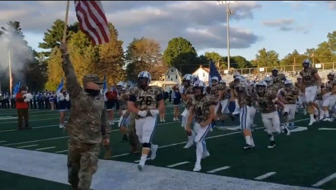 Members of the armed forces escort the Louisville High School football team onto the field last season. Louisville was one of 10 schools designated as Purple Star for its commitment to serving students and families connected to the military.