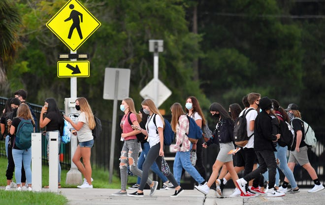 Sarasota High School students cross School Ave. as the first bell rings Monday morning, Aug. 31, 2020 on the first day of school in Sarasota County.