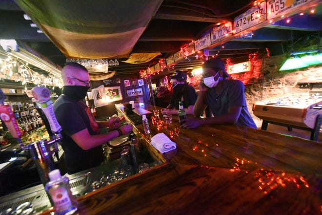 Bob Hejnas serves up some drinks inside Lula's Pub in downtown Wilmington in early October. Area businesses are adjusting to enforcement of mask wearing in accordance of COVID-19 protocols.