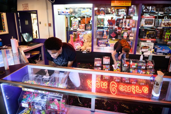 Aaron Lightfoot, left, and Julie Kelly work on cleaning things up at Omni Family Amusement Center on Thursday. The amusement center and Omni Cinemas are scheduled to reopen  Oct. 9.