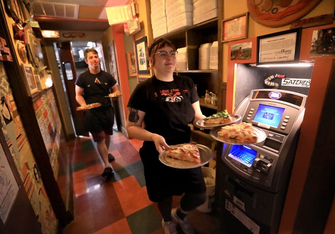 Members of the wait staff carry plates to customers at Satchel's Pizza in January.