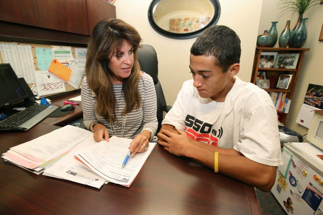 A school counselor talks with a student in a photo taken before the coronavirus pandemic.
