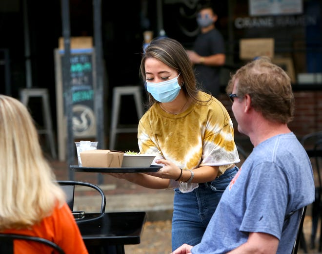 Erica Allen, a waitress at Crane Ramen restaurant in downtown Gainesville, carries a meal to Curtis and Heather Weatherall in the outside eating area set up on Southeast First Avenue on Friday. Minimum wage employees, like waitresses who work mostly for tips, could be greatly affected by a change to the minimum wage via a proposed amendment on the November ballot.