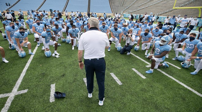 North Carolina coach Mack Brown meets with the Tar Heels after their victory against Syracuse in the Sept. 12 season opener. [The Associated Press]