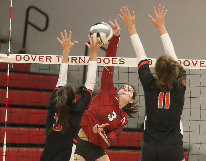 New Philadelphia's Kiera Sexton and Maddy Hooper go for a block as Dover's Taylor Luneborg spikes the ball in Thursday's match. (TimesReporter.com / Jim Cummings)