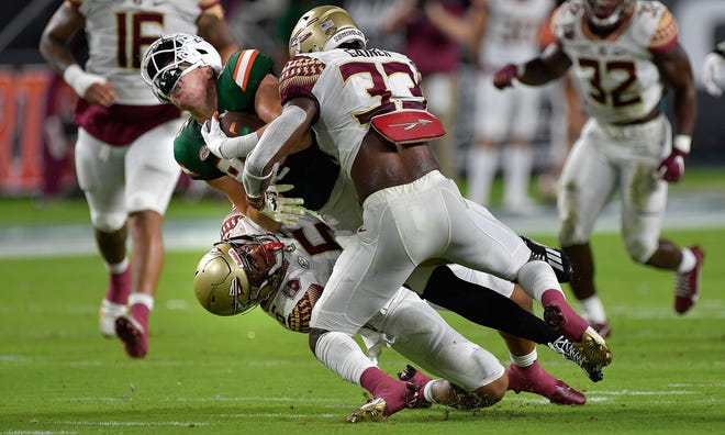 Miami tight end Will Mallory is sandwiched between Florida State defenders Jaiden Lars-Woodbey and Amari Gainer during the first half of an NCAA college football game, Saturday, Sept. 26, 2020, in Miami Gardens, Fla. (Michael Laughlin/South Florida Sun-Sentinel via AP)