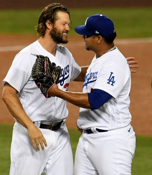 Dodgers Clayton Kershaw, left, hugs Brusdar Graterol after defeating the Milwaukee Brewers 3-0 in Los Angeles on Thursday, October 1, 2020. Kershaw notched the win with eight innings and Graterol recorded the save.