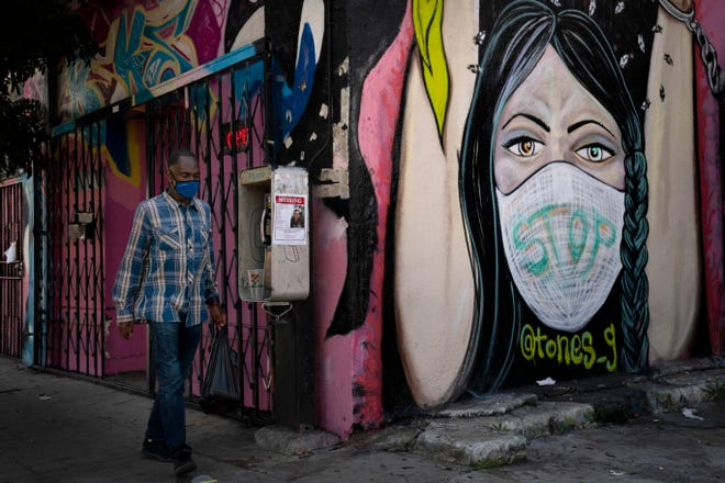 A man wearing a face mask walks past a mural Thursday, Oct. 1, 2020, in South Central Los Angeles.