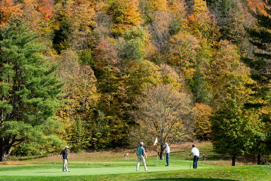 Golfers putt out on the eighth green at Woodstock Country Club during the Division II boys golf championship qualifier on Thursday, Oct. 1, 2020.