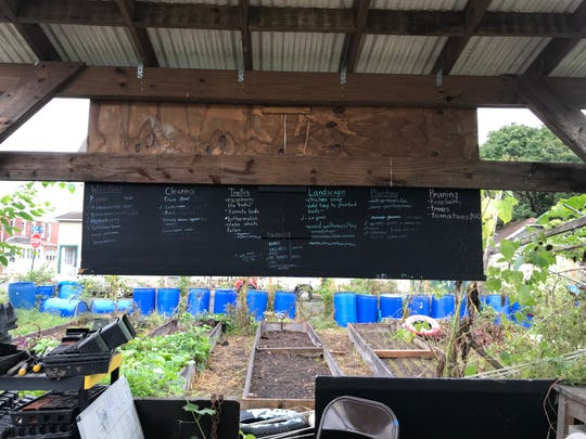 A board keeps track of what needs to be done at VietLead's garden in East Camden: weeding, landscaping, harvesting, and more.