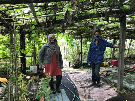 Lan Dinh and Naajia Shakir stand under a trellis at Resilient Roots Farm in East Camden. Dinh and Shakir work with student farmers to teach them agriculture and leadership.