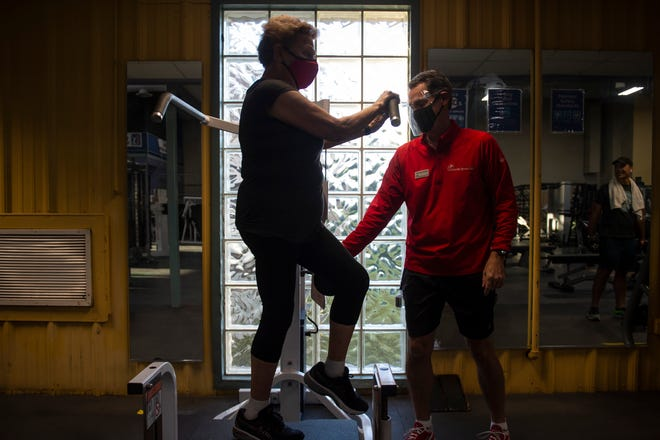 Personal trainer Brad Messenger instructs Doloris Learmonth while she trains with him at Cincinnati Sports Club in Fairfax on Friday, Oct. 2, 2020. Learmonth has been training with Messenger for about 20 years.