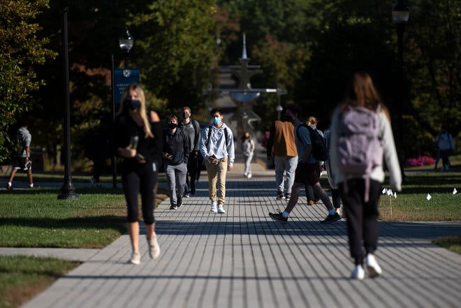 Students walk across campus wearings masks at Xavier University in Norwood on Friday, Oct. 2, 2020.