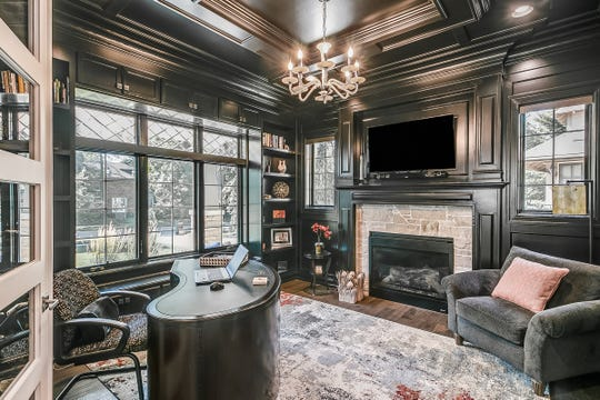 The lavish office is lined with layer after layer of crown molding and more trim, all painted very dark. It has a large stone fireplace and a view of the front street. Its window is topped with diamond-pattern beveled glass.