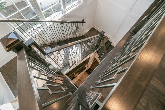 The sophisticated staircase -- three stories of metal and wood -- runs from the second floor to the lower level.