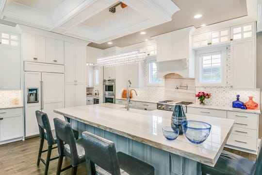 The big, open kitchen measures 18 by 18 and has the extensive trim that characterizes this house. Lighted glass-door cabinets overhead add dash.
