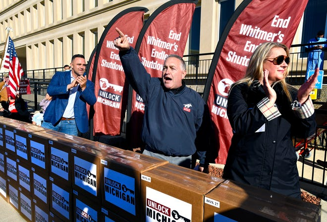 Unlock Michigan co-chairs, from left, Garrett Soldano, Ron Armstrong and Meshawn Maddock speak to supporters in Lansing in October 2020.