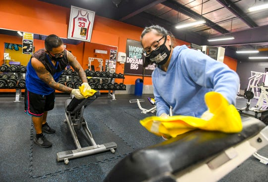 Shift Supervisor Geana Silvestri, front, and Fitness Attendant Marvin Espeleta, wipe down and sanitize equipment in the free-weight section of the Paradise Fitness gym in Dededo on Friday, Oct. 2, 2020. In the latest round of lifted restrictions by Gov. Lou Leon Guerrero, gyms, fitness centers and dance studios will be allowed to resume indoor operations, but each will be subject to limits of no more than 25% occupancy load and must abide to applicable Department of Public Health and Social Services guidance. Paradise Fitness, with locations in Hagåtña, Tumon and Dededo, is preparing its facilities to reopen and welcome back its patrons beginning 8:00 a.m., Saturday morning.