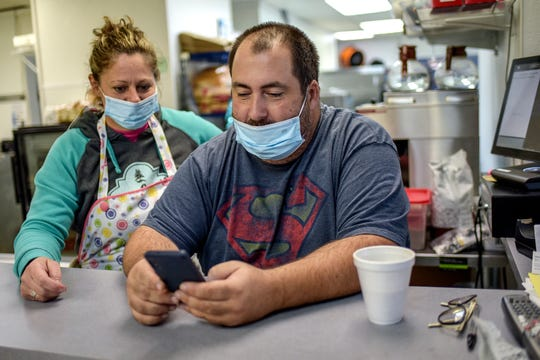 Owner Denny Emmer, right, and his wife Michelle look on his phone on Thursday, Oct. 1, 2020 for a replacement window for the one that was damaged during a break-in at Cheezy D's Deli and Dogs in Haslett after business hours on Sept. 30.