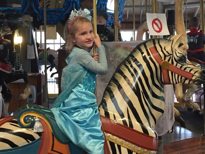 """Natalie Benton, 5, dressed as Elsa from the movie """"Frozen"""" to ride the backwards carrousel."""