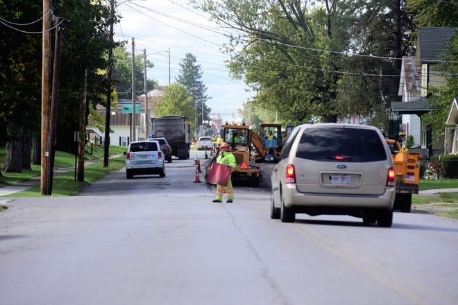 A flagger stops traffic on Harding Way in Galion as crews mill pavement.