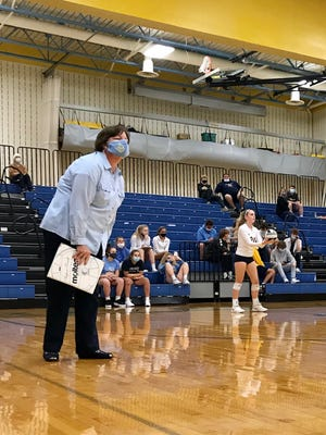 River Valley volleyball coach Jayne Klingel coaches in a mask from the sideline as fans in the stands also wear masks during a match with Pleasant this fall.