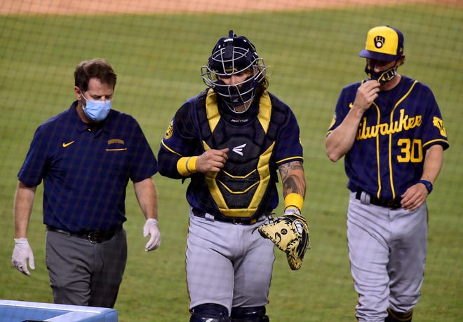 Brewers catcher Jacob Nottingham is accompanied by Manager Craig Counsell and a trainer  as he leaves the game with a hand injury in the sixth inning.
