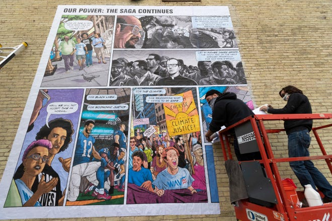 Steve Roche, left, and Brett Waterhouse hang a mural depicting the struggles Milwaukee has faced for the last 50 years including racism, fair housing marches and income inequality October 2, 2020, at the intersection of S. 5th and W. Walker Streets in Milwaukee, Wis. Poster-sized versions of the mural will be hung across the city. The installation is part of a program sponsored by March for Our Lives Wisconsin, 50 Miles More, Wisconsin Anti-Violence Effort Educational Fund (W.A.V.E.), and Youth Empowered in the Struggle (YES).