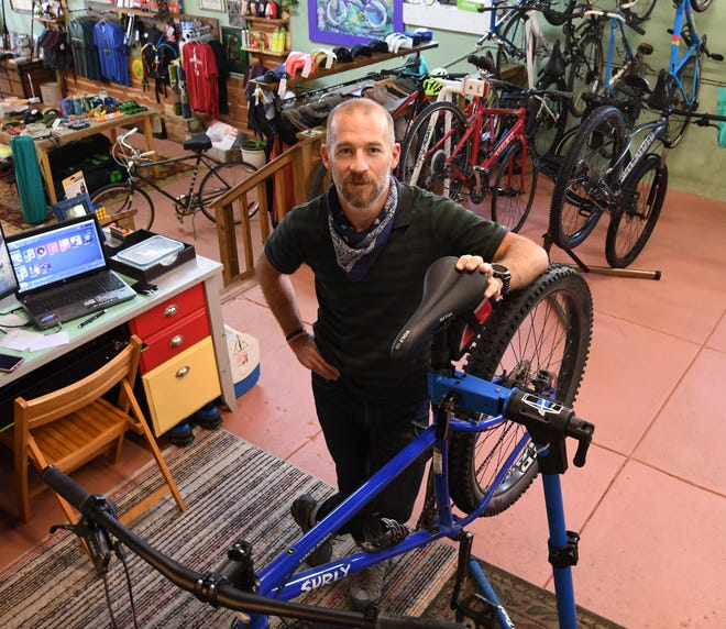 Jake Anderson, owner of Norfork Adventure Supply, stands next to a bicycle suspended on a repair rack in the bicycle shop portion of the store. The business has been selling and servicing bikes since last November.