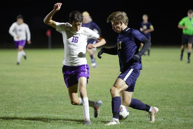 Delta's Luke Burkle slips past Muncie Central's Sam Voss during their match Wednesday, Sept. 30, 2020. Delta won 4-1.