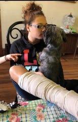 Isabella dihibur oleh anjing penolongnya, Zoey, setelah kaki dan pergelangan kakinya patah tahun lalu.