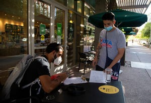 Issac Perez, a canvaser for Mi Familia Vote, helps ASU student Amontá Jones register to vote outside of a Starbucks on the ASU Downtown Phoenix campus on Oct. 2, 2020. This is Jones's first time registering and this upcoming election will be his first time voting, and he is currently undecided. Credit: Meg Potter/The Arizona Republic