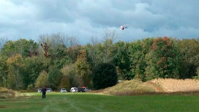 A helicopter circles the site of a small plane crash near Corfu, Genesee County, Oct. 2. The crash killed pilot Stephen Barnes and his niece Elizabeth Barnes.