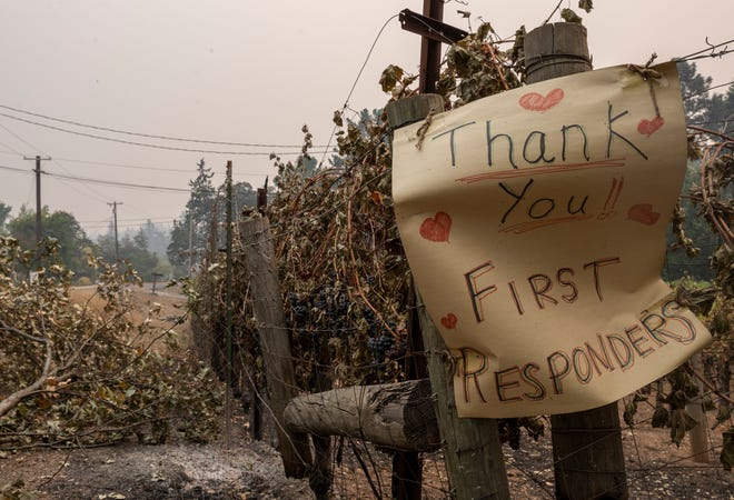 """A sign that reads """"Thank you first responders"""" hangs near a vineyard that has been damaged by the Glass Fire in Napa County on Thursday, Oct.1, 2020."""
