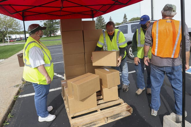 Volunteers grab boxes of food during a drive-thru mobile food pantry on Thursday, Sept. 10, 2020, in Wisconsin Rapids, Wis. The distribution event was hosted by Feeding America of Eastern Wisconsin.