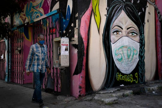 A man wearing a face mask walks past a mural on Thursday in South Central Los Angeles.