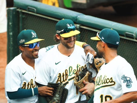 Victorious A's players, from left, Tony Kemp, Chad Pinder and Marcus Semien celebrate after advancing past the White Sox in the AL wild card round.