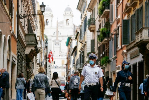 City police officers wearing masks patrol shopping street Via Condotti in Rome, Friday, Oct. 2, 2020.