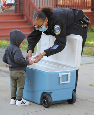 Akron Police Officer Crystal Carter passes out snacks to Mason Ellis, 1, Oct. 2 on Storer Avenue as part of the Snack With a Cop program. A new citywide effort will bring together focus groups to discuss ways police and the community can improve ties in the wake of protests that swept the nation last year.