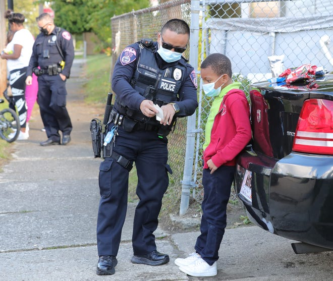 Akron police officer Damber Subba passes out a police badge sticker to Trevon Barclay, 8, on Madison Avenue after giving him a few snacks in October as part of their Snack With a Cop program.