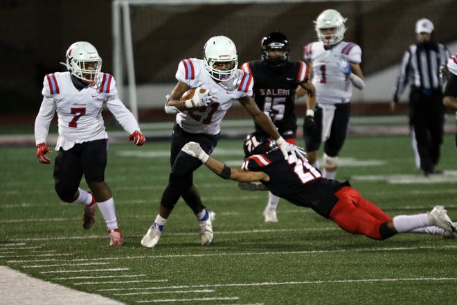 Alliance's Kayden Davis makes a cut around end as Salem's Jax Booth goes for the tackle. Alliance's Tre Hawkins (7) looks on.