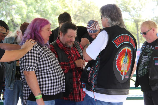 Members of Bikers for Christ, a Christian ministry for motorcyclists, and the Densmore family join together in a prayer before embarking on their march at Regional Park Saturday morning.
