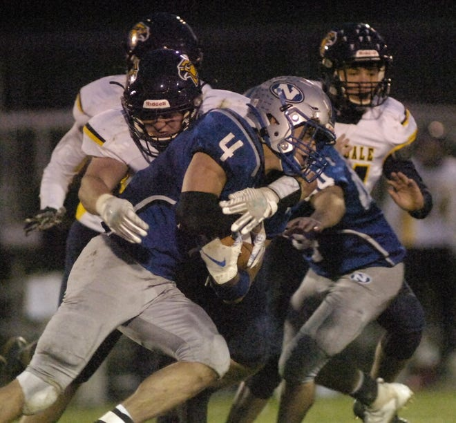 Northwestern's Hal Huber (4) gets wrapped up with Hillsdale's Ty Williams (9) during high school football action Friday at Northwestern High School. The Huskies defeated the Falcons, 22-15.