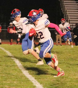 Mapleton's Kaleb Stafford (22) returns an interception for a touchdown during the game against New London Friday at Recreation Park. The Mounties won, 65-26.