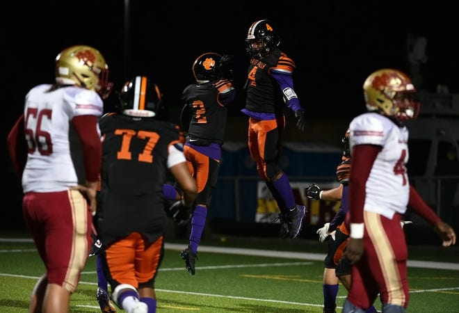 Beaver Falls' Tyler Jones (4) celebrates with teammate Trey Singleton (2) after he intercepts a New Brighton pass and runs it in for a touchdown in the second quarter of their game Friday at Reeves Field.