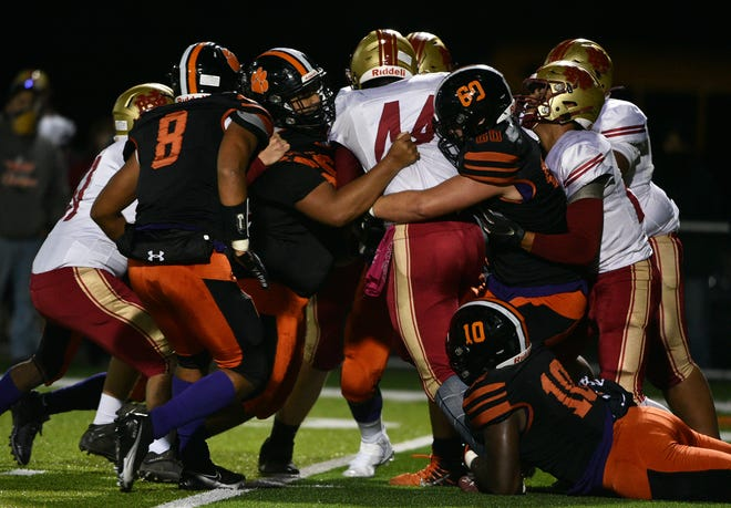 New Brighton's Kei'Ondre Abercrombie is brought down by a team of Beaver Falls players Friday during their game at Reeves Field.