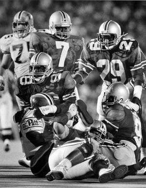 """Linebacker Thomas """"Pepper"""" Johnson leads a swarm of Ohio State tacklers against Pittsburgh in the first night game in Ohio Stadium history, on Sept. 14, 1985. The Buckeyes won 10-7 in a game that ushered in a new era of OSU football, in which television dictates starting times. [Dispatch file photo]"""