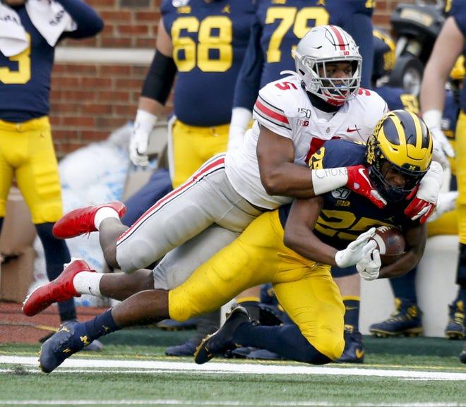 Ohio State linebacker Baron Browning tackles Michigan running back Hassan Haskins on Nov. 30 in Michigan Stadium.